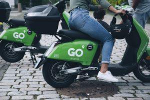 Abbildung des hinteren Bereiches eines E-Mopeds von Go Sharing, auf dem eine Frau sitzt. Unten Kopfsteinpflaster